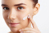Attractive girl putting anti-aging cream on her face. Closeup Portrait Of Girl With Healthy Smooth Skin