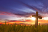 Wooden cross on green grass with sunset
