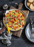 Vegetable frittata in a cast iron skillet on wooden background. Delicious brunch, top view