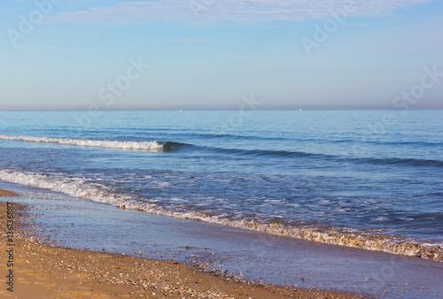 Costa Blanca sandy beach in winter, Valencia region, Spain. Gentle waves bring shells on the beach.