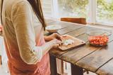 Mujer cortando cebolla con cuchillo en una table de madera antigua.