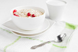 Rolled oats, porridge and cranberries for a healthy breakfast in a rustic style