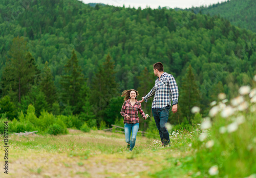 Poster Young couple in love walking in mountain.