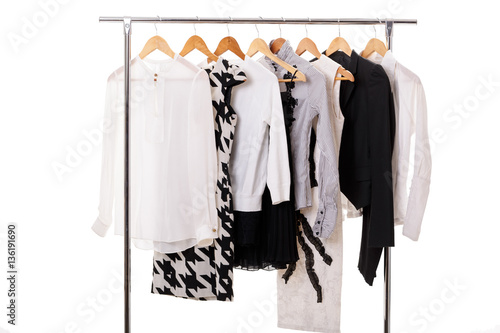 3072fdd3945 black and white womens clothes on hangers on rack on white backg ...