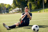 injured soccer player with ball on football field - 136196089