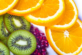 Healthy food for active life, fruits. Sliced oranges and kiwi, pomegranate seed. Orange slices arranged on a circle. White background.
