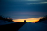 One small travelling car silhouetted on a hilltop of a highway at sunset in a winter landscape