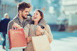 Beautiful young loving couple carrying shopping bags