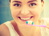 woman brushing cleaning teeth. Girl with toothbrush in bathroom.
