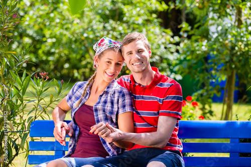 Poster Paar im Garten sitzt auf Bank