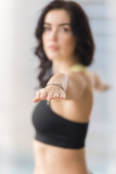 Young attractive woman practicing yoga, standing in Warrior Two exercise, Virabhadrasana II pose, working out, wearing sportswear, black tank top, focus on fingers, looking at the camera, closeup
