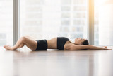 Young sporty woman practicing yoga, lying in Reclined Butterfly exercise, supta baddha konasana pose, working out, wearing sportswear, black tank top, shorts, full length, floor window with city view