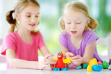 Two cute little sisters having fun together with modeling clay at a daycare. Creative kids molding at home. Children play with plasticine or dough.