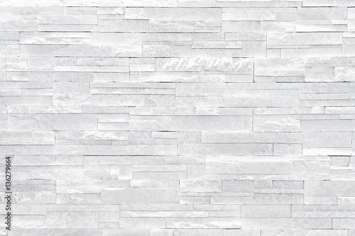 Foto op Canvas Stenen White stone wall background. Stacked stone tiles are often used in interior design decors as accent wall. Use this gray texture in graphic design to create a wallpaper, background, backdrop and more!