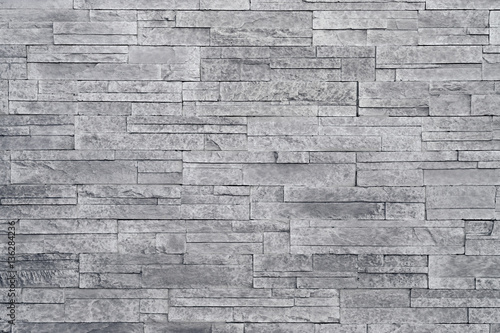 Poster Stenen Grey stone wall background. Stacked stone tiles are often used in interior design decors as accent wall. Use this gray texture in graphic design to create a wallpaper, background, backdrop and more!