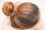 Top view of woman head with tied her hair.