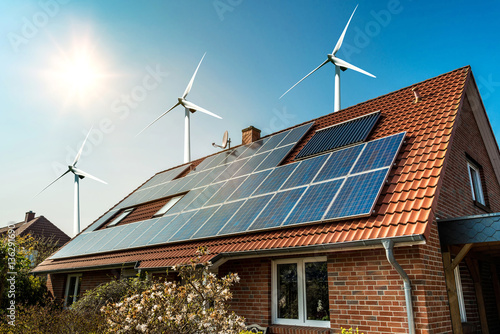 Solar panel on a roof of a house and wind turbins arround - concept of sustainable resources