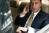 Fototapety Businessman Talking Using Phone Car Inside