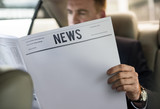 Fototapety Businessman Reading Newspaper Car Inside