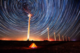 Circles in the night sky / Long time exposure night landscape with star trails over a wind farm