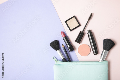 Make up products spilling out of a pastel blue cosmetics bag, on a pink and purple background with blank space at side - 136296893