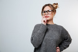 Pensive beautiful young woman in glasses standing and thinking