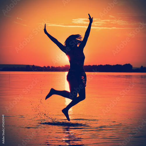 Plexiglas Koraal Silhouette of a woman jumping in the water at sunset
