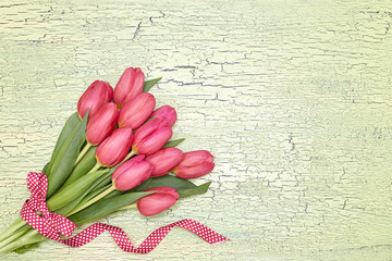 Red tulips bouquet decorated with ribbon on green background. Copy space, top view