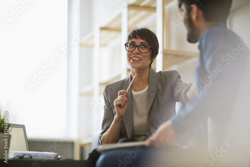 Two cheerful colleagues smiling while discussing something in modern office, foc Poster