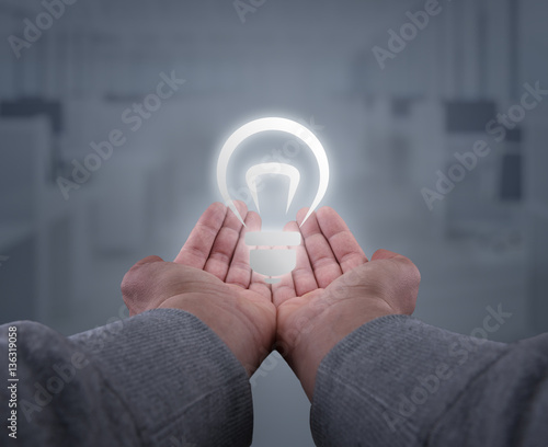 hands holding up a light bulb