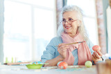 Attractive senior woman painting Easter eggs at home