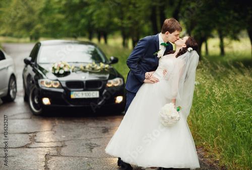 Couple kissing near the car плакат