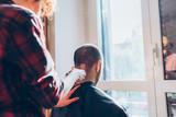 Woman barber cutting hair using razor - beauty, hair style concept