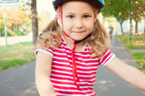Pretty little child girl ride and having fun with bicycle in par