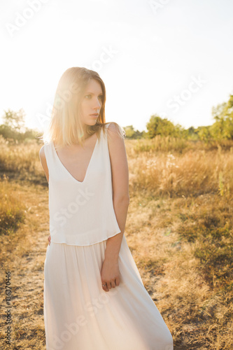 Poster Beautiful blonde woman in a long white dress posing in the field