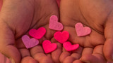 Childrens hands holding the heart on a pink background. Concept of love, care, faith, hope, purity.