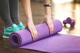 Close-up of attractive young woman folding yoga or fitness mat a