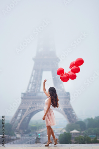 Parisian woman with red balloons in front of the Eiffel tower Poster