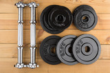 Disassembled dumbbells on wooden table
