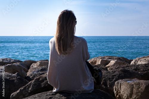 donna seduta di spalle sugli scogli guarda il mare Poster