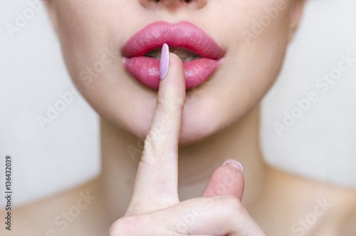 Woman with pink lipstick and finger showing hush silence sign, gesture and beauty concept, gray background Poster