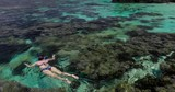 Young woman snorkeling over coral reef on a tropical island