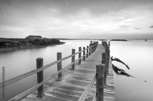 Ancient pier and abandoned boat at black and white fine art photography  © Henrique Silva