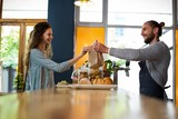 Woman receiving parcel from waiter at counter