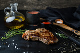 Grilled steak t-Bone on a plate with sauce, olive oil and rosema