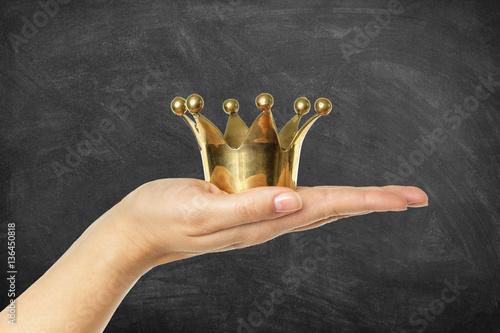 Poster Goldene Krone auf Hand vor Schultafel