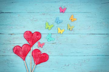 rote Herzen (Lollipops) mit bunten Schmetterlingen