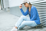 Young girl sitting on skateboard with mobile phone and headphone against modern gray wall.