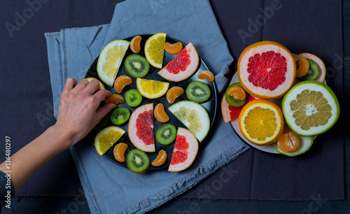 she takes from a plate with a piece of fruit, Mandarin, citrus, orange, tangerine, kiwi, brightly colored on a blue grey kitchen towel, cloth dark background