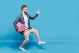 Young man in casual clothing creeping secretly with pink gift box in hand on blue studio background.